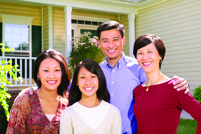 A Happy Family Standing in Front of a House