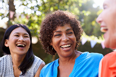Multicultural group of middle-aged women smiling and laughing, showing off white teeth