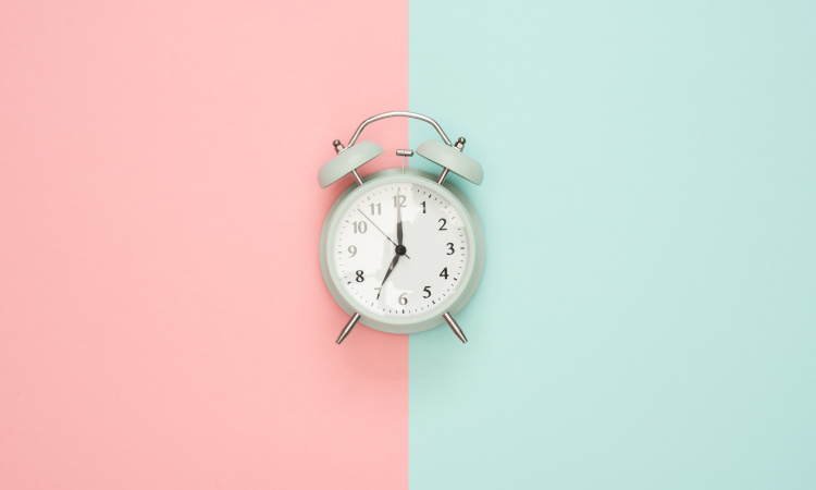 Old-fashioned silver alarm clock at 7:00 against a pink and blue background