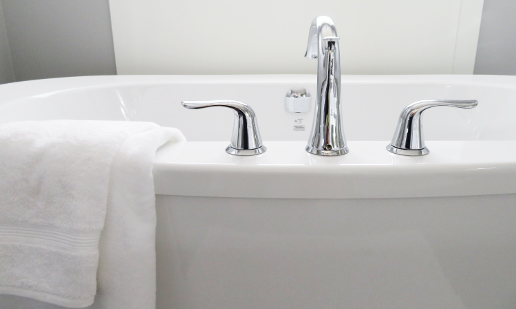 Closeup of a white bathtub with a silver faucet with a white fluffy towel draped over the side