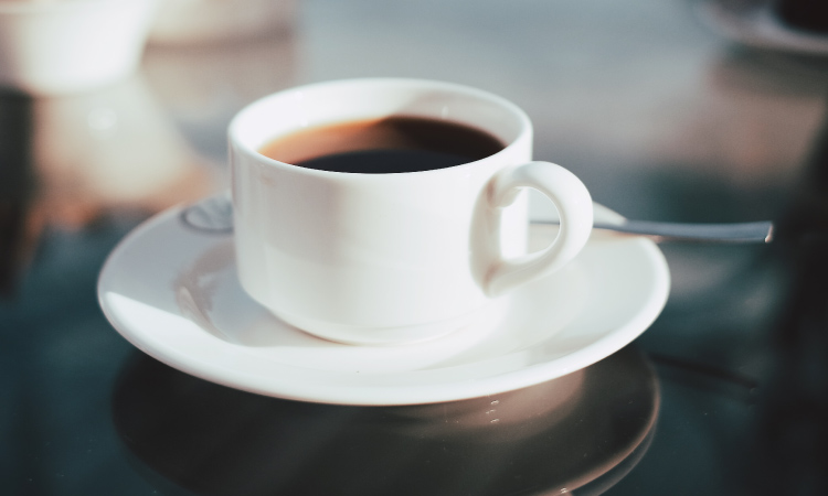 Closeup of a white mug and saucer with black coffee with caffeine next to a silver spoon
