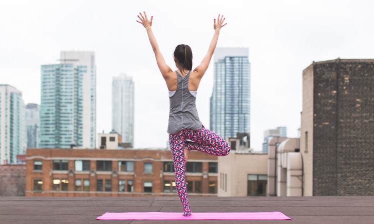 Back view of brunette woman on one leg in a yoga pose with her hands reached to the sky overlooking a city skyline