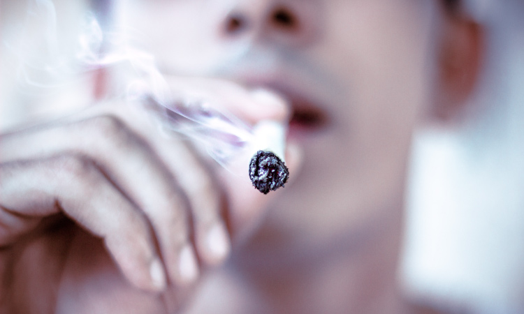 Closeup of a man smoking a dangerous cigarette that will cause bad breath and tooth discoloration