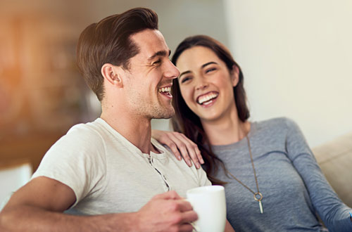 A couple laughing while enjoying a cup of coffee together