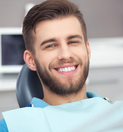 A young man smiling while sitting comfortably in the dental chair